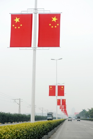 A row of Chinese flags in the middle of the road.   Stock Photo - 13691776