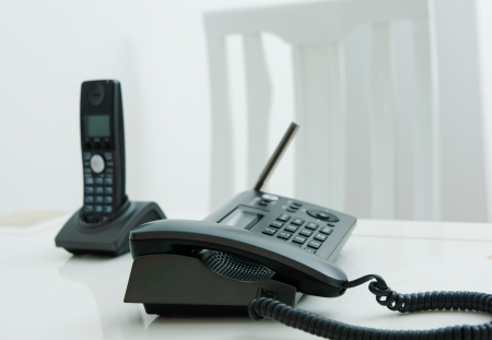 conference call: Close up of two business phone with white chair in the background.