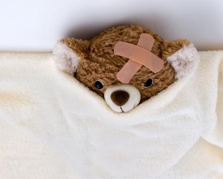 Teddy bear ill in bed photo