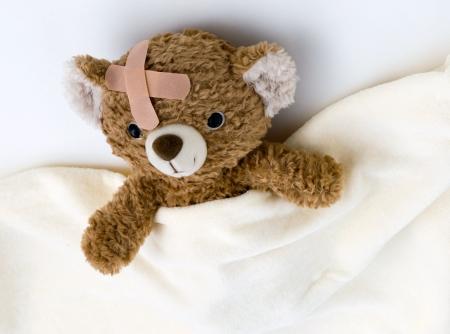 lesionado: Oso de peluche enfermo en la cama