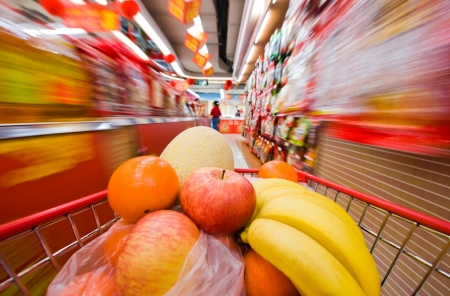 Moving shopping cart, and shot with a slow shutter from the shopper's point of view. The fruits in the shopping cart is in focus, and the supermarket is motion-blurred.   photo