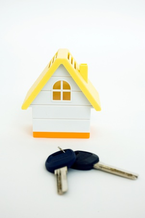 Concept image of a house and keys isolated on white background  The miniature model house with house keys beside it   photo
