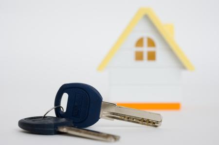 Concepto de imagen de una casa y las llaves aisladas sobre fondo blanco La casa modelo en miniatura, con llaves de la casa al lado de él Foto de archivo - 14481528