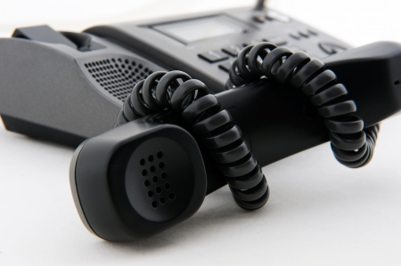 telephony: Black telephone receiver winded by telephone line. Stock Photo
