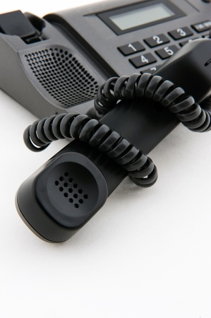 muddle: Black telephone receiver winded by telephone line. Stock Photo