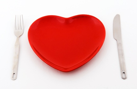 empty red heart plate with knife and fork on a white background. photo
