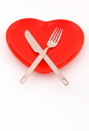 arteries: empty red heart plate with knife and fork on a white background.