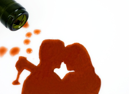 wine bottle on the side with spilled wine in shape of kissing man and woman silhouette.    photo