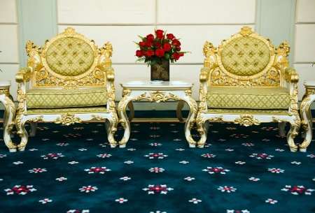 Two antique chairs and marble table, and bouquet of red roses placed in the middle of them.  photo