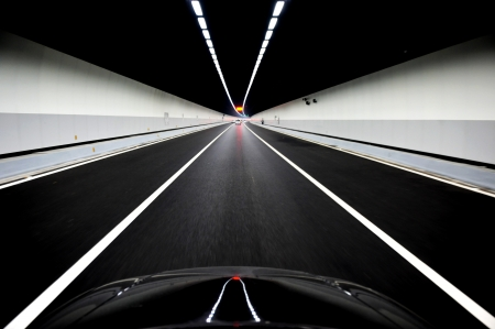 inside car: Cars on road in tunnel with lights overhead.  Stock Photo