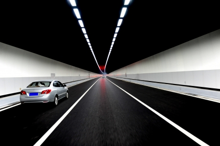 tunnel view: Car zooming through a tunnel.