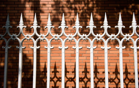 white steel picket fence in front of brick wall.  photo