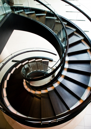 wooden railings: black spiral staircase in restaurant with shiny wooden handrail.  Editorial