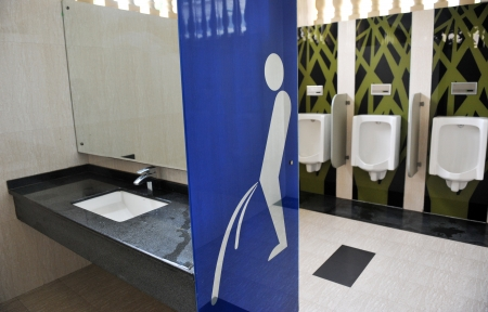 urination: Urinals in modern office building, with Wc icon.