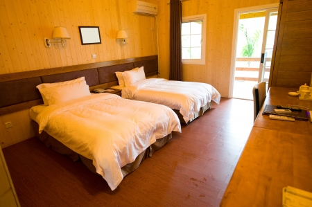 Wooden hotel room with two beds.