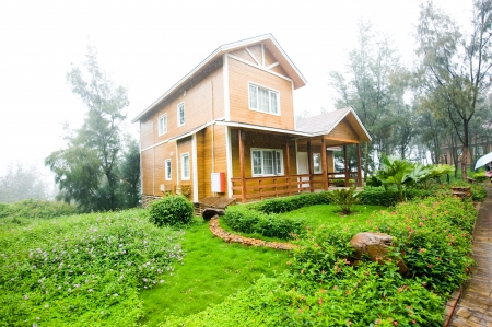 A wooden house  with garden in the rain. Stock Photo - 13744744