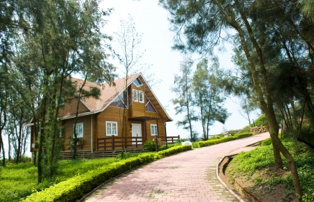 A wooden house beside curving lane and surrounded by many trees.