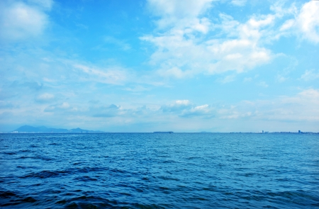 water level: Blue sky and sea with slight cloud. Stock Photo