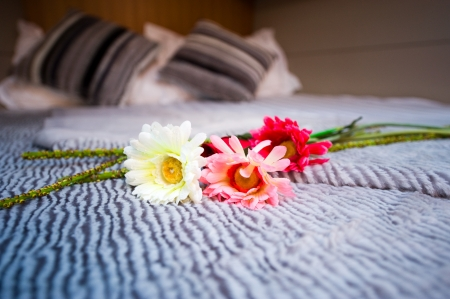 Three flowers on a bed with grey sheets.  photo