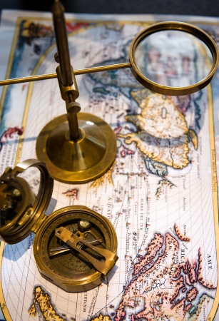 An old brass compass and magnifier on old world background.