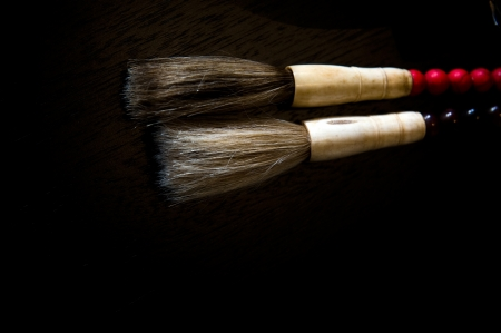 ideogram: Chinese calligraphic brushes with hair for the brush on black background.  Stock Photo