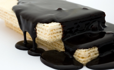 coated: Lots of chocolate falling to the surface of wafer biscuits.