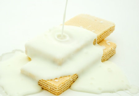 coated: Lots of white chocolate falling from above to the wafer biscuits.  Stock Photo