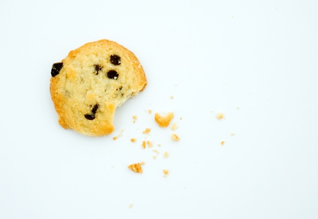 missing bite: Top view of chocolate chip cookie with a bite taken out and crumb scattered around, isolated on a white background.