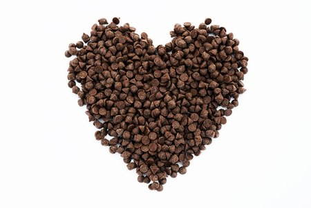 chocolate chips arranged into a heart shape and isolated on white.  photo
