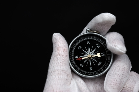 azimuth: Hand holding the compass isolated on black background.  Stock Photo