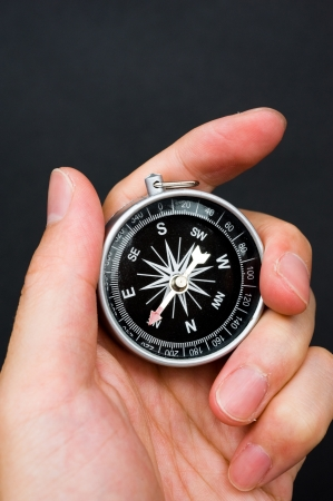 Hand holding the black compass isolated on black background. Stock Photo - 13780851
