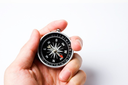 coordinate: Hand holding the black compass isolated on black background.