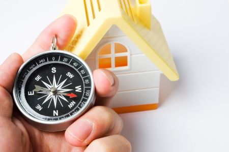 Hand holding the black compass beside small house model. Stock Photo - 13780353