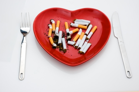 noxious: isolated heart shape plate with cigarettes. Stock Photo