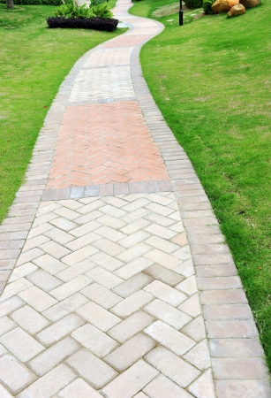 curve brick path in garden, and surrounded by green grass.