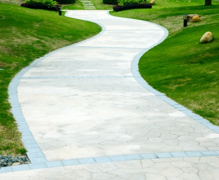 garden path: curve stone path in garden, and surrounded by green grass.  Stock Photo