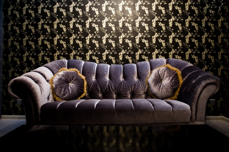 Modern purple sofa with two cushions in front of beautiful wallpaper.  photo