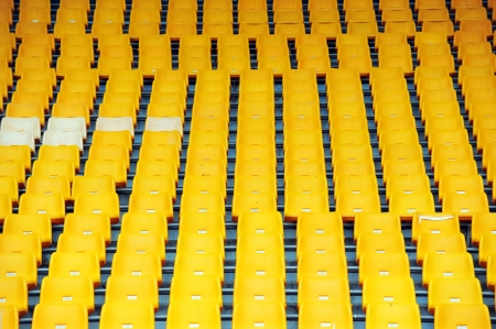 Rows of yellow football stadium seats with numbers.  photo