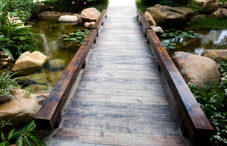 wooden railings: simple wooden bridge over a stream.
