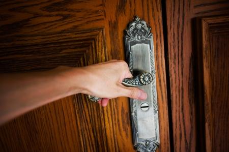 puerta abierta: Mano en una puerta de mango de madera para abrir o cerrarla.