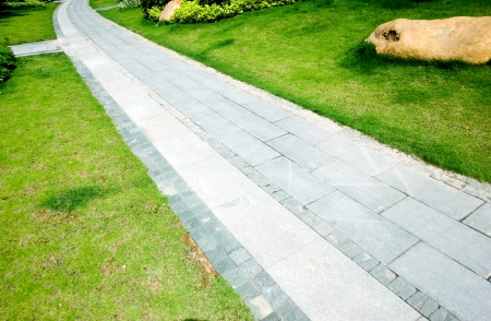 curve stone path in garden, and surrounded by green grass. Stock Photo - 13781312