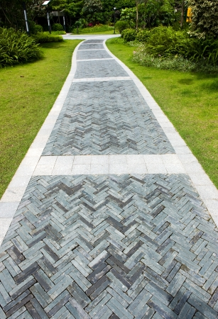 curve brick path in garden, and surrounded by green grass.  photo