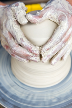 Potters hands creating a clay masterpiece at the turning wheel.  photo