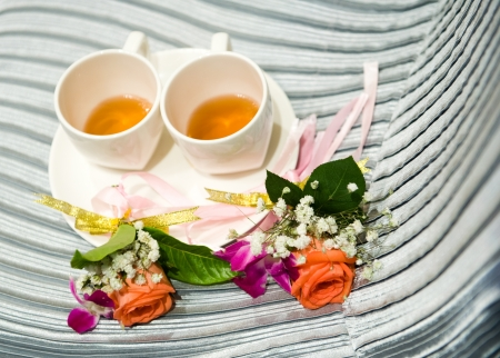 free plate: two cup of tea on the surface of chair, with two roses beside them.  Stock Photo