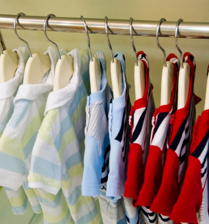 A row of summer clothes hanging on hangers.   photo