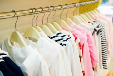 ropa colgada: Una fila de la ropa de los ni�os cuelgan en perchas.