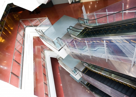 view of a staircase in a shop: interior of modern business building with escalators. Editorial