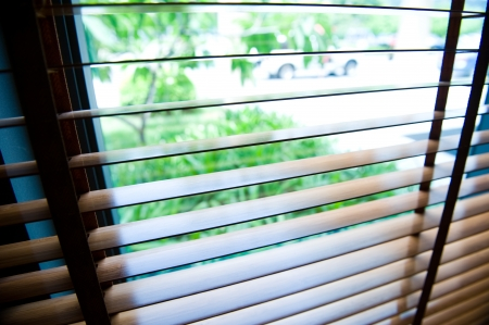 blinds inside a window being opened to show sunlight. photo
