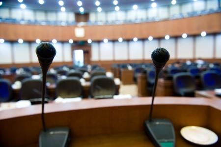 hablar en publico: antes de una conferencia, los micrófonos en frente de sillas vacías.