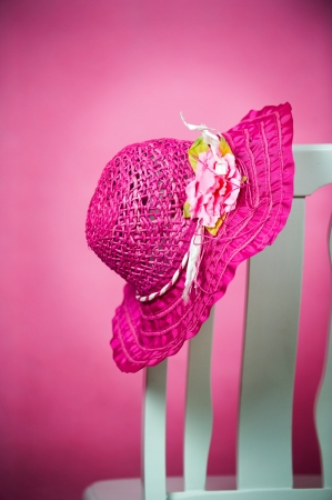 pink hat: pink summer hat on chair isolated on pink background. Stock Photo